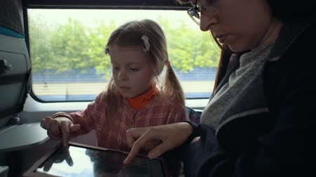 compartimento : Mother and little daughter are playing on the touchpad.They sitting by the window in moving train. Stock Footage