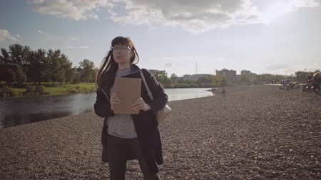 베이지 색의 : Young brunette woman with tablet computer in her hands is dancing on the background of pebble beach. Businesswoman in glasses uses touchpad in beige case on river bank. 무비클립