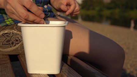 noedelsoep : Close up of female hands picking up piece of chicken with wooden chopsticks. Young woman in checkered shirt sits on wooden deck chair on pebble beach and eats noodles from takeaway box Stockvideo