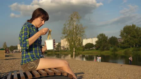 seixo : Young brunette woman eats instant noodles from white box using chopsticks, girl in blue checkered shirt and beige shorts barefoot sits on wooden deck chair on pebble beach Stock Footage