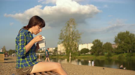 seixo : Side view on young brunette woman eats instant noodles from white box using chopsticks, girl in blue checkered shirt and beige shorts barefoot sits on wooden deck chair on pebble beach