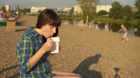 chaise longue : Young brunette woman eats instant noodles from white box using chopsticks, girl in blue checkered shirt and beige shorts barefoot sits on wooden deck chair on pebble beach Stock Footage