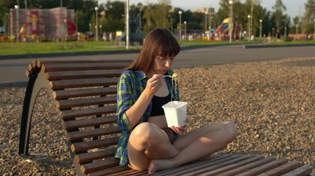 conveniente : Girl eats instant noodles from white box using chopsticks, brunette in blue checkered shirt and beige shorts barefoot sits on wooden deck chair on pebble beach, against blurred people, handheld shot Stock Footage