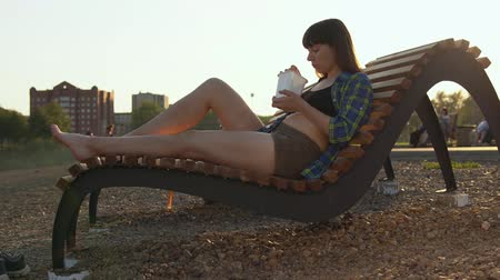instante : Girl eats instant noodles from white box using chopsticks, brunette in blue checkered shirt and beige shorts barefoot sits on wooden deck chair on pebble beach, against blurred people, handheld shot Stock Footage