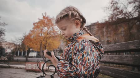 úttest : Portrait of little cute blond girl in colored jacket playing an application using smartphone. Child sits on bench next to city road amid yellow foliage of trees.