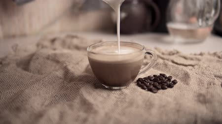 brew : An unknown person pours foamy milk into a glass cup to a hot aromatic dark coffee. Someone is preparing latte at home. Stock Footage