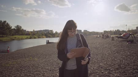 бежевый : Businesswoman in glasses uses touchpad in beige case on river bank. Concept of remote work around the clock on weekends.Young brunette woman with tablet computer goes on pebble beach.