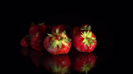 výřez : Close-up of lot red ripe strawberries are turning around on a mirror surface, seamless loops. Ugly organic berries isolated on a black background. Dostupné videozáznamy