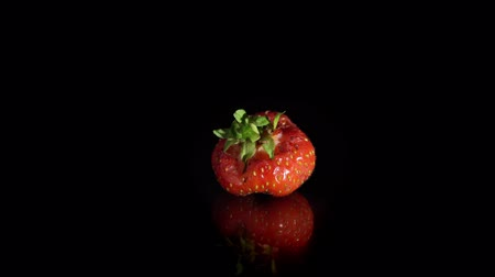 výřez : Close-up of one ugly red ripe strawberries are turning around on a mirror surface, seamless loops. Fresh juicy berries isolated on a black background.