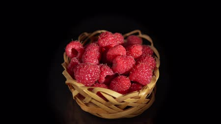 výřez : Close-up of pile of ripe raspberries in small wicker basket are turning around on a mirror surface, seamless loops. Fresh red juicy berries isolated on a black background. Dostupné videozáznamy