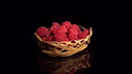 black raspberry : Pile of ripe raspberries in small wicker basket are turning around on a mirror surface, seamless loops. Fresh red juicy berries isolated on black background.