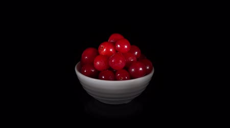 výřez : Pile of ripe wet cherries in small white cup are turning around on a mirror surface, seamless loops. Fresh red juicy berries isolated on a black background. Dostupné videozáznamy