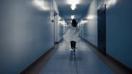scatters : Tracking shot of zombie woman with black hair in laboratory coat walks down dark corridor goes behind door and falls,view from back. Above doorway inscription in Russian exit.