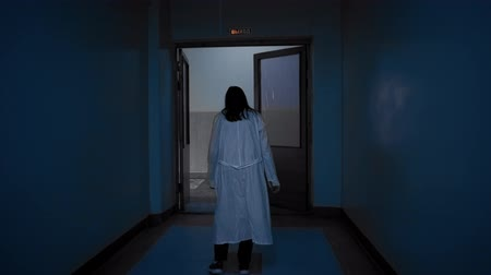 bizarre : Tracking shot of zombies girl with black hair in a white robe walks down a dark corridor to the door,view from back.