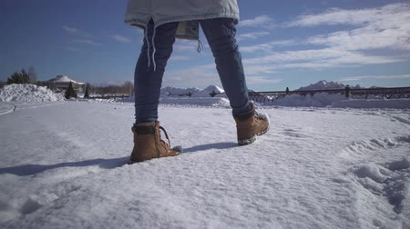 pegada : Low angle womans feet in jeans and warm shoes walking in the snow on winter sunny day,handheld shooting.
