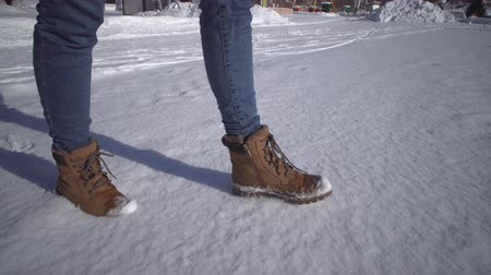 süet : Low angle womans feet in jeans and warm shoes walking in the snow on winter sunny day,handheld shooting.