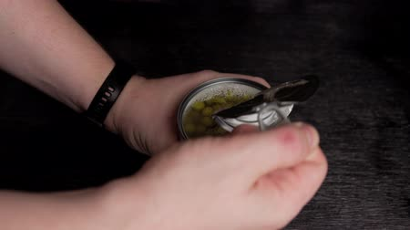lids : Male hands open metal tin can with green pea on black background.