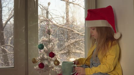 hófúvás : Child in red Santa Claus hat holds hot cocoa and plays with blue shiny ball. Little blond girl sits on windowsill next to white artificial Christmas tree, outside on snow branches, dolly shot.