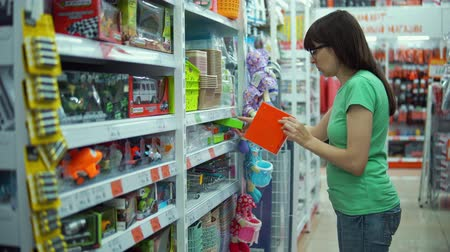 lids : Brunette girl chooses colored plastic container with lid for needlework in department of household goods in supermarket.