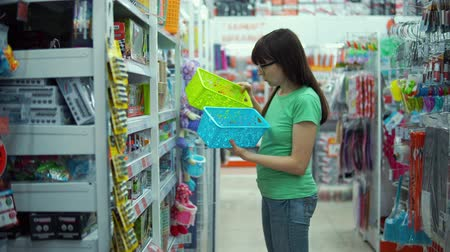 buyer : Brunette girl chooses plastic basket for organizing storage of things at home in chest of drawers or closet in department of household goods supermarket.