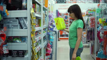 srovnávat : Young woman chooses plastic basket for organizing storage of cosmetics products at home in chest of drawers, closet or in bathroom in department of household goods supermarket.