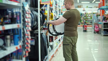 repuestos : Young muscular man chooses new steering wheel cover in car accessories department store.