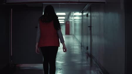 vluchteling : Camera follows young brunette woman in red sleeveless jacket walks quickly along long corridor with low ceilings in the dark.