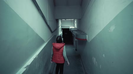 vluchteling : Back view of young brunette in red sleeveless jacket descends down long staircase in dark old corridor, tracking shot. Stockvideo