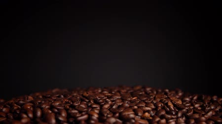 cooling : Pile of roasted coffee beans rotates on a black background. Drying and preparation for grinding to prepare a fragrant drink, place for text. Stock Footage