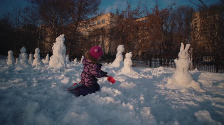 ileri : Little cute girl in lilac suit plays with snowdrifts. Happy child makes snowman next to snow sculptures on warm sunny winter day.