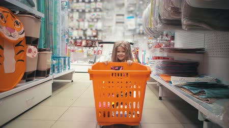 скрывать : Happy child with long blond hair hides behind an orange trolley between the shelves of hardware store. Little cute girl plays with shopping cart in supermarket.