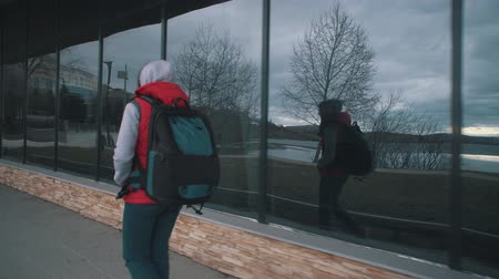 percepção : View from the back of young brunette woman in red sleeveless jacket is walking alongside large windows on cloudy day. Girl carries backpack and is reflected in glass of building, tracking shot. Stock Footage