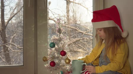 顔写真 : Little blonde girl in red Santa Claus hat blows hot cocoa in blue mug.Child sits on windowsill next to white artificial year tree decorated with colored balls, outside on branches of snow, dolly shot. 動画素材