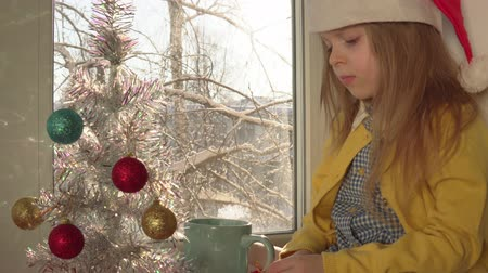 bombki : Child in red Santa Claus hat blows hot cocoa in blue mug.Little blonde girl sits on sill next to white artificial Christmas tree decorated with colored balls, outside on branches of snow, dolly shot.