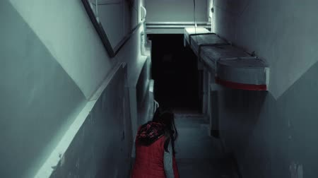 trappenhuis : Back view of young brunette in a red sleeveless jacket quickly descends down long staircase in dark corridor, tracking shot.