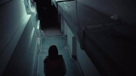бункер : Top view tracking shot of young brunette in red sleeveless jacket descends down long staircase in dark old corridor. Стоковые видеозаписи