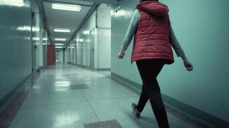 коридор : Camera follows young brunette woman in red sleeveless jacket walks quickly along long corridor with low ceilings in the dark, tracking shot.