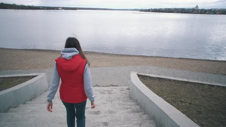 seixo : Back view of young brunette in red sleeveless jacket walking down the steps to calm lake on cloudy day,tracking shot. Stock Footage