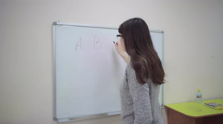 calcular : Female teacher stands at whiteboard and explains rules of addition in elementary school. Caucasian schoolmaster in glasses writes examples with marker on blackboard.