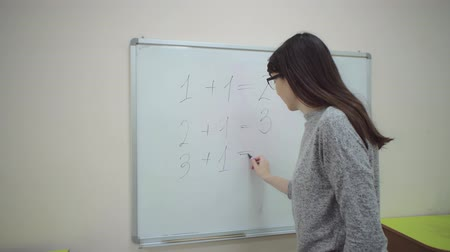 calcular : Female teacher stands at chalkboard and explains rules of addition in elementary school. Caucasian schoolmaster writes simple examples of sum with black marker on whiteboard.