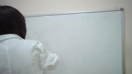calcular : Girl in a lab coat writes in black marker on whiteboard general formula for electrolysis of water. Vídeos