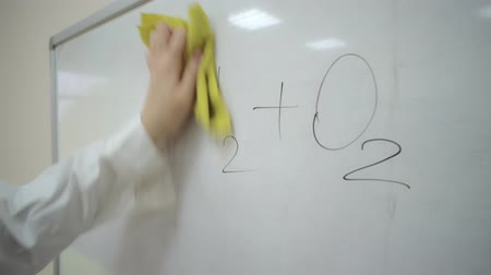 calcular : Camera follows girl in a lab coat who erases the general formula for electrolysis of water from whiteboard.