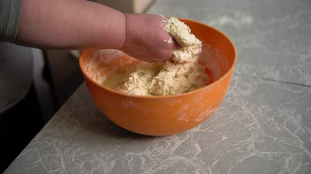 pite : Close-up of female hands kneading yeast dough in an orange bowl on the kitchen table. Stock mozgókép