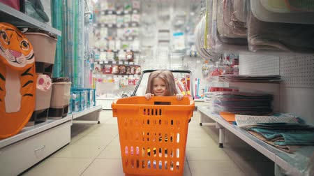 przedszkolak : Happy child with long blond hair hides behind an orange trolley between the shelves of hardware store. Little cute girl plays with shopping cart in supermarket.