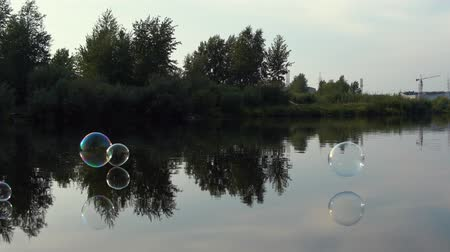 glide : Huge soap bubbles fly over the river. The balls glide over the mirrored surface of calm water.