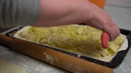 pite : Close-up of female hands put butter slices on raw cake, the process of making homemade potato pie.