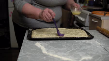 batido : Grandma with silicone brush smears beaten egg on raw cake, the process of making homemade potato pie. Stock Footage