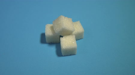 sweetener : White refined sugar turns on a blue background. Pile of square pieces of crystal sweetener revolves on a cyan plate.