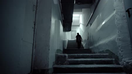 respirator : Frightened young woman with blue protective gas mask in red sleeveless jacket descends the dark stairs to the basement protected from man-made disasters. Stock Footage