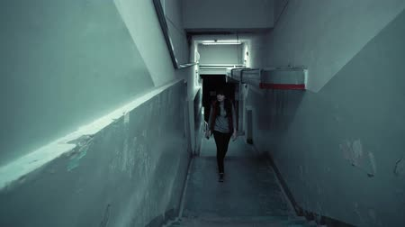 trappenhuis : Young frightened woman in red sleeveless jacket is climbing the stairs in dark corridor with shabby walls, an old ventilation pipe stretches under the ceiling. Stockvideo